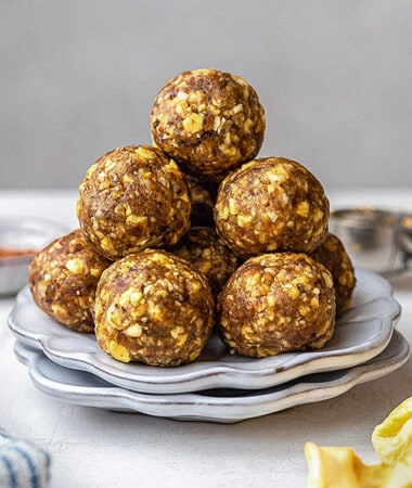 Side view of a stack of 6 apple protein balls on a white plate
