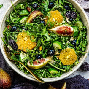 Top view of a healthy mixed arugula salad in a white bowl with figs + citrus