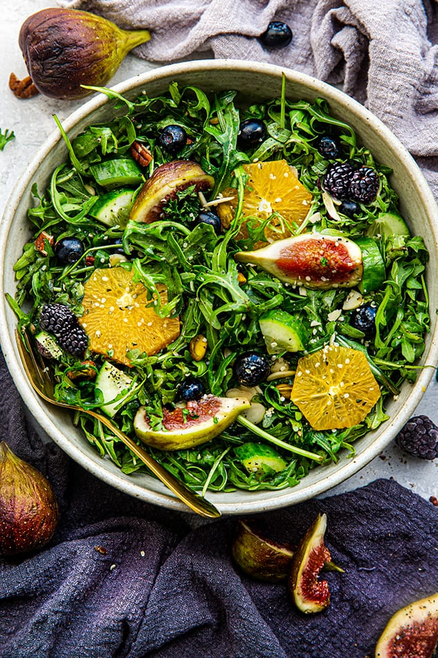 Overhead view of a bowl of Arugula Salad with figs, berries, and oranges
