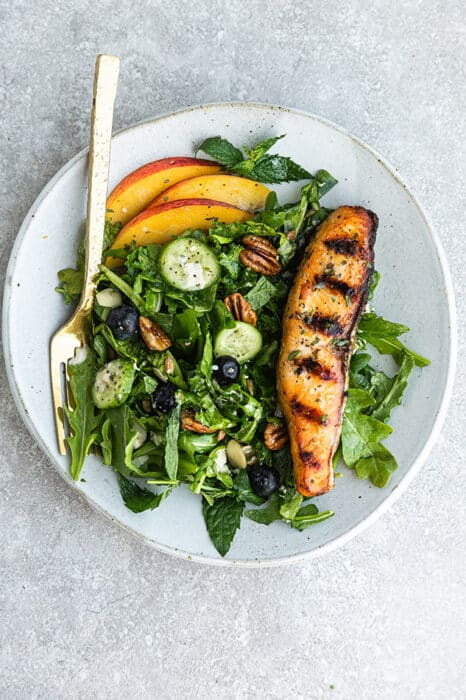 Top view of arugula salad with peaches, blueberries and grilled salmon on a white plate on a grey background