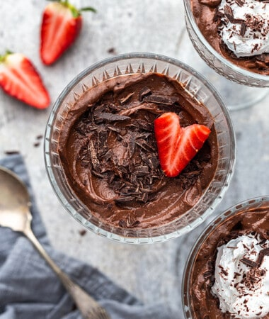 Avocado Chocolate Pudding in three glass jars with a strawberry