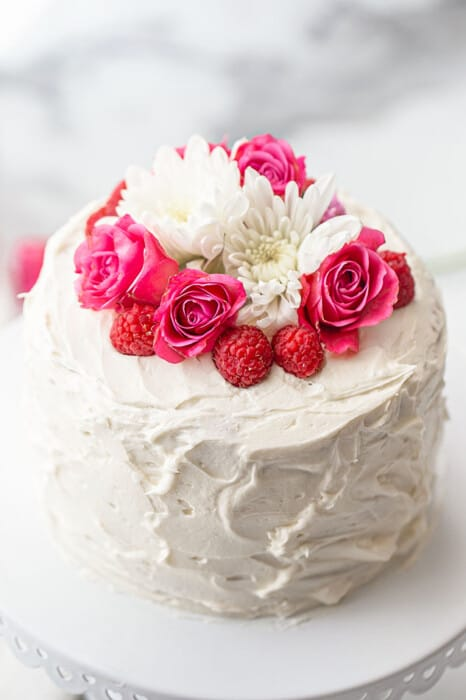 A whole Keto Vanilla Cake topped with fresh flowers and raspberries on a white cake stand