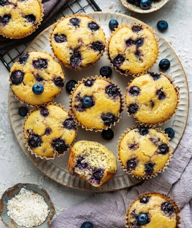 Overhead view of Lemon Blueberry muffins on a plate with a bite out of one