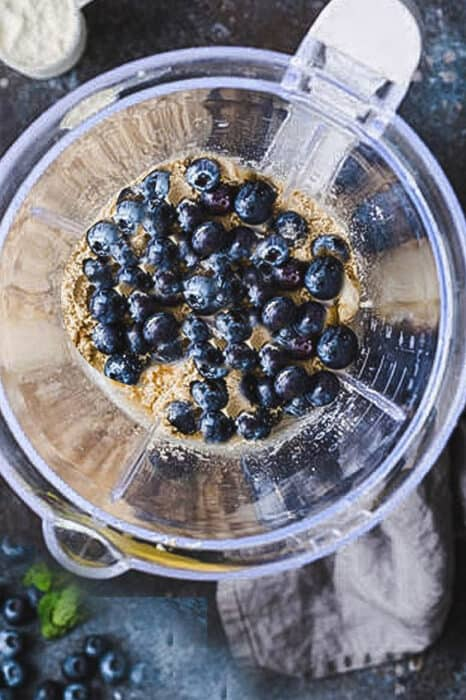 Top view of blueberries and optional protein powder in a blender in preparation to make a blueberry protein smoothie
