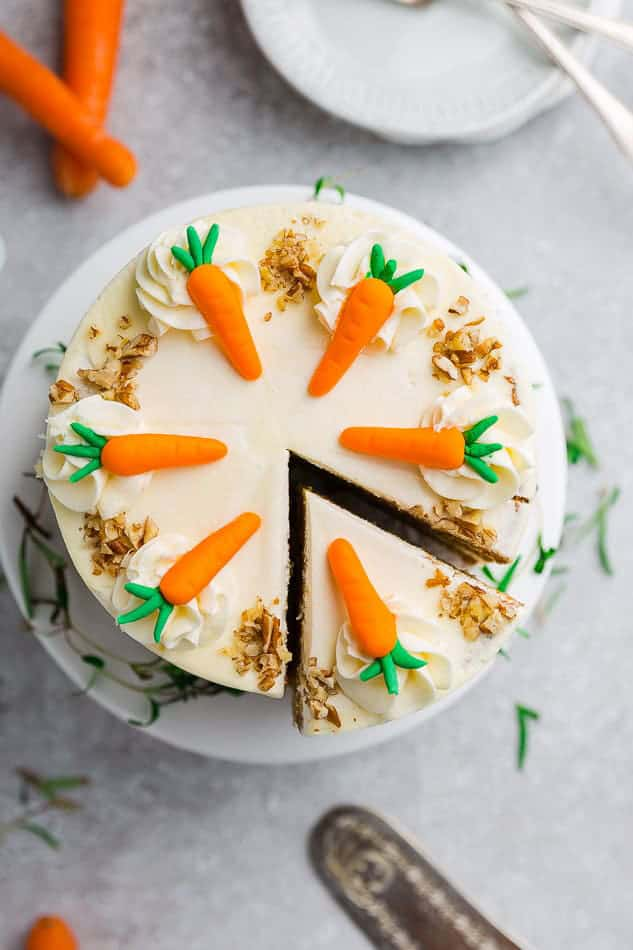 Overhead view of Gluten Free Carrot cake with icing carrot decorations and a slice cut