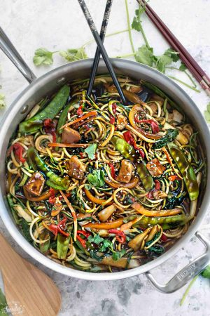 Healthy Chicken Chow Mein Zoodles  with delicious red bell peppers, peas  and chicken in a large silver skillet with beautiful black and gold chopsticks.