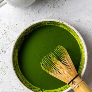 Whisked matcha powder in a white bowl with a bamboo whisk