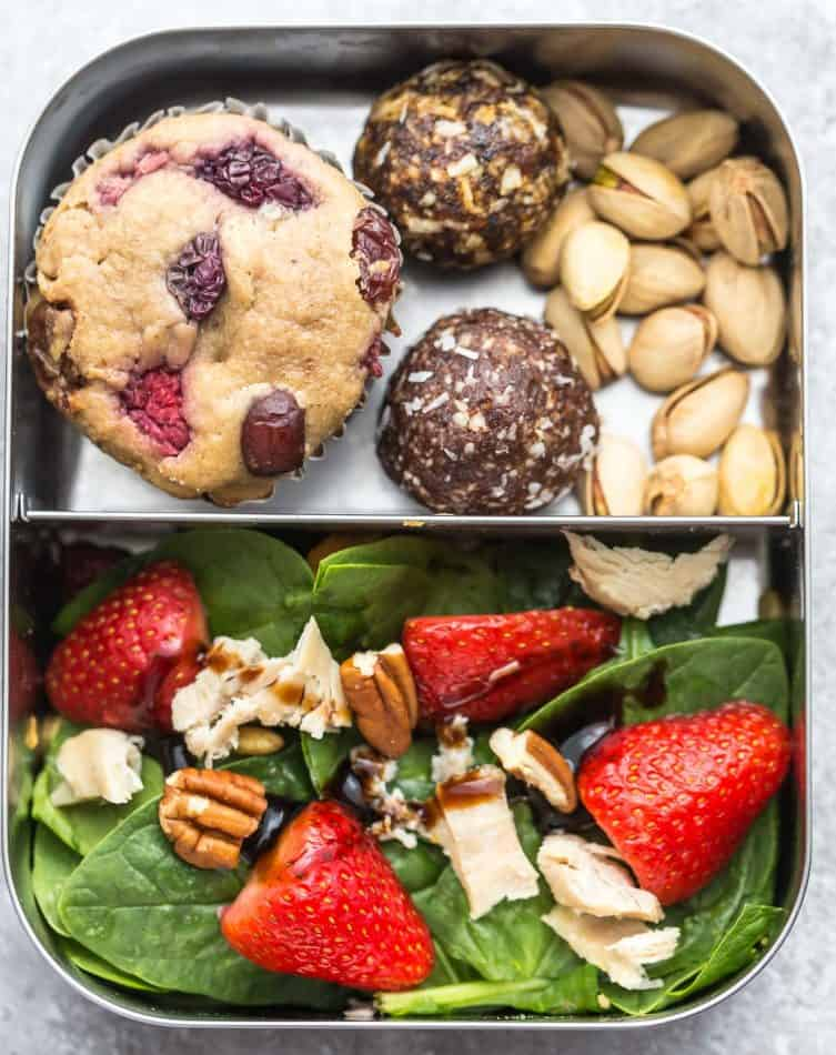 Lunchbox of a strawberry muffin, energy balls, pistachio nuts and spinach strawberry salad