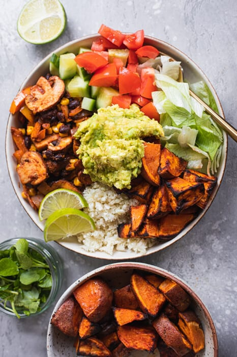 Top view of vegan burrito bowl on a grey background with toppings