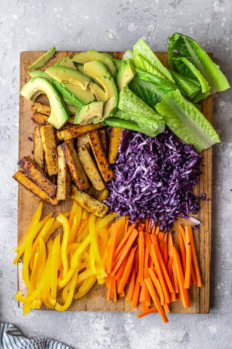 Top view of sliced vegetables on a wooden cutting board to make easy summer rolls