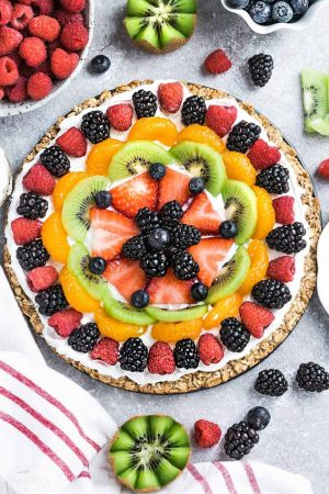 Top view of Healthy Fruit Pizza on parchment paper with berries and a white plate