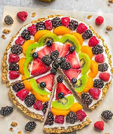 Top view of Healthy Fruit Pizza on parchment paper with 2 sices cut