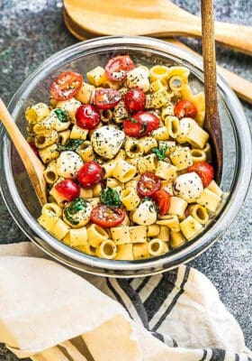 Top view of gluten free caprese pasta salad in a clear mixing bowl with two wooden spoons