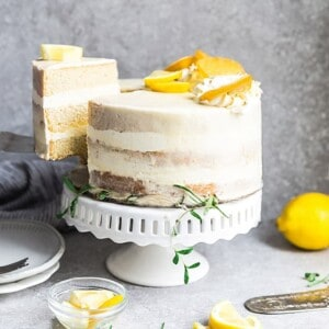 Side view of one healthy lemon cake on a white cake stand with one slice cut out