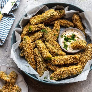 Side top view of keto avocado fries in a blue bowl with avocado dip on a grey background