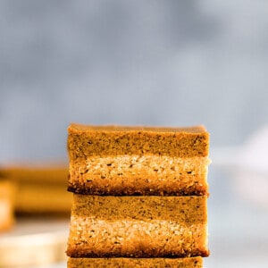 Side view of three keto pumpkin pie bars stacked on top of each other