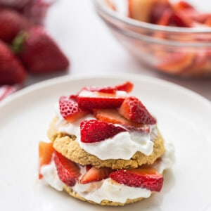 Portrait view of one gluten free strawberry shortcake on a white plate