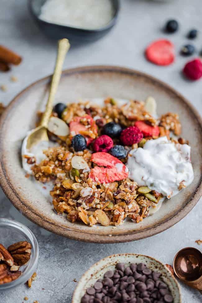 Side view of healthy granola in a white bowl with a gold spoon with yogurt and berries