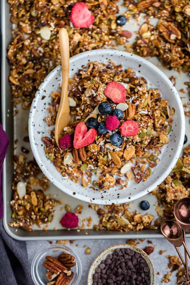 Top view of healthy granola in a white bowl on a baking sheet