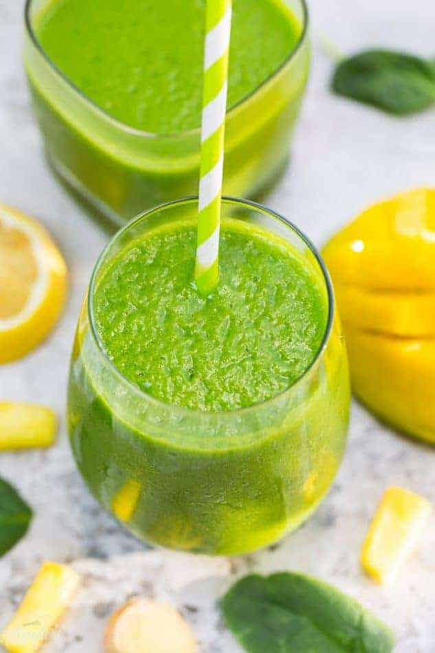 Top view of one healthy spinach smoothie in a clear glass with a straw on a grey marble background with fruit