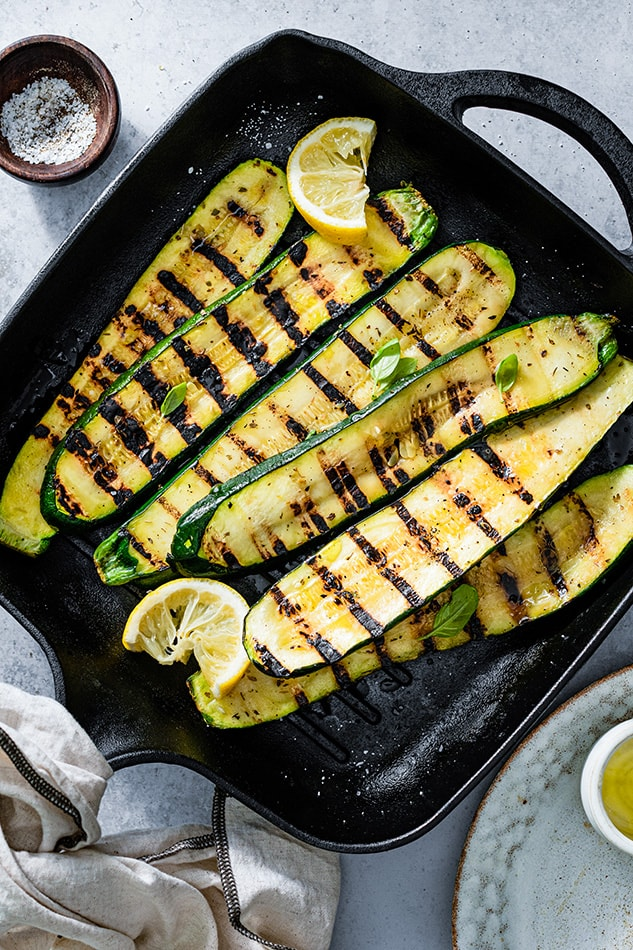 Top view of grilled zucchini on cast iron with lemon wedges.