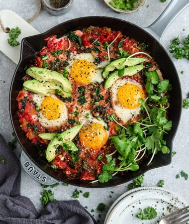 Top view of healthy shakshuka in a grey cast-iron skillet on a grey background with forks