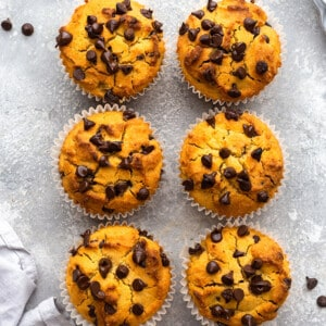 Top view of 6 healthy pumpkin muffins scattered on a grey background