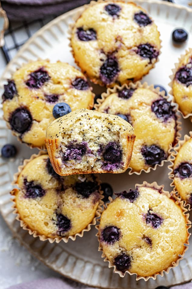 Overhead view of a plate of Lemon Blueberry muffins with a bite out of one