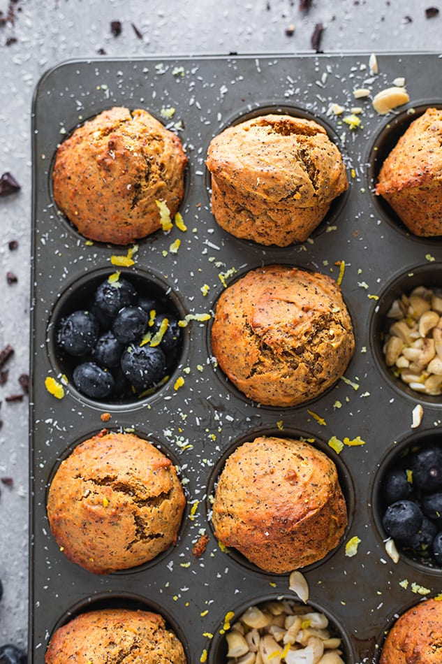 Overhead view of Lemon Poppyseed Muffins in a tin garnished with fresh blueberries