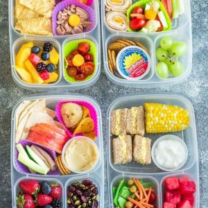 Four school lunch ideas in clear bento lunchboxes on a grey background