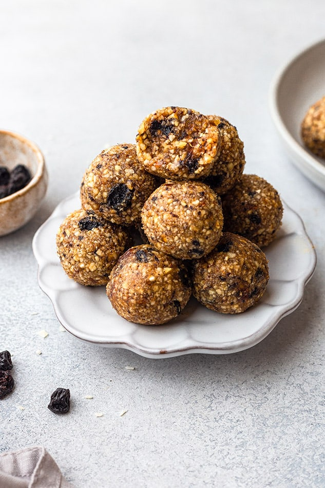 Side view of a pile of blueberry protein balls on a white plate