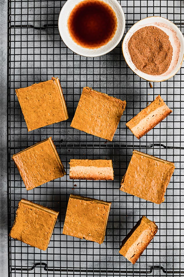 Top view of 9 healthy pumpkin bars scattered on a black wire rack