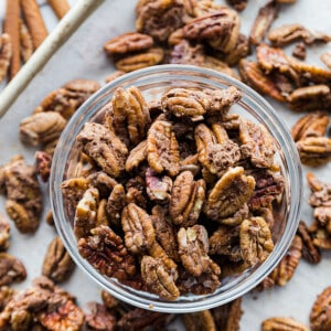 Top view of healthy roasted pecans in a clear bowl on a baking pan