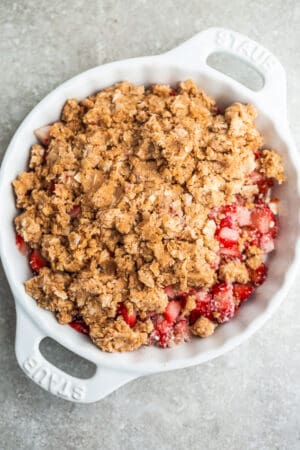 Top view of strawberry rhubarb crisp topping and strawberry filling in a white pie pan