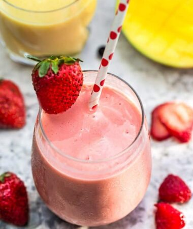 Top view of one healthy strawberry smoothie in a clear glass with a straw on a grey marble background with fruit