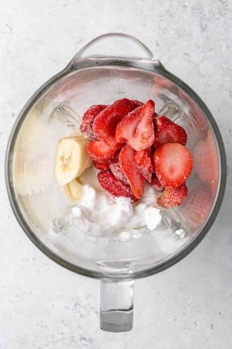 Top shot of frozen strawberries, coconut cream and milk in a blender