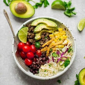 Taco Bowl in a white bowl with corn, tomatoes, beans and avocado