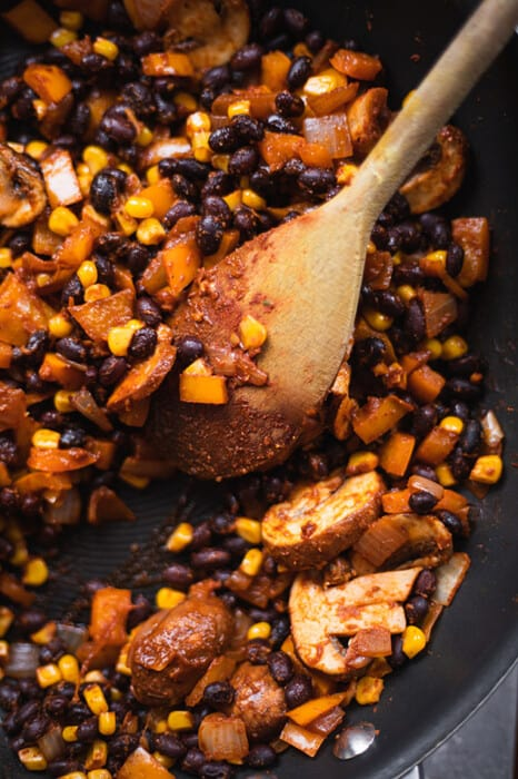 Skillet of black beans and corn with a wooden spoon