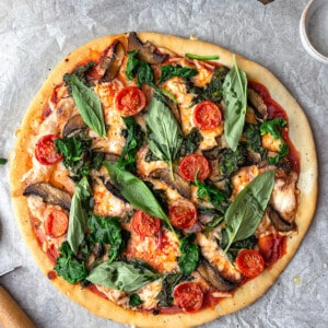 Top view of a whole vegetable pizza on parchment paper with a wooden knife