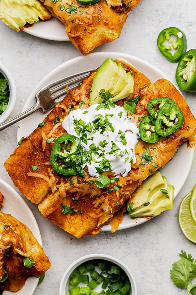 Overhead view of a serving of vegetarian enchiladas on a plate topped with avocado, jalapeno, sour cream and cilantro