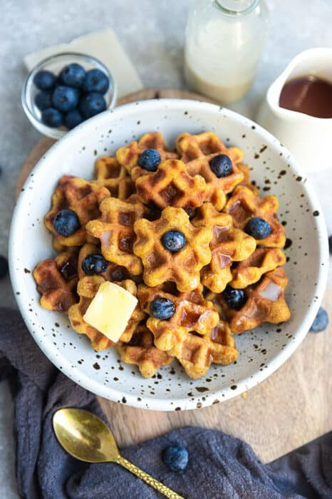 Top view of healthy waffle cereal in a white bowl with blueberries, butter, milk and maple syrup