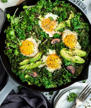 Top view of healthy green shakshuka in a grey cast-iron skillet on a grey background with forks