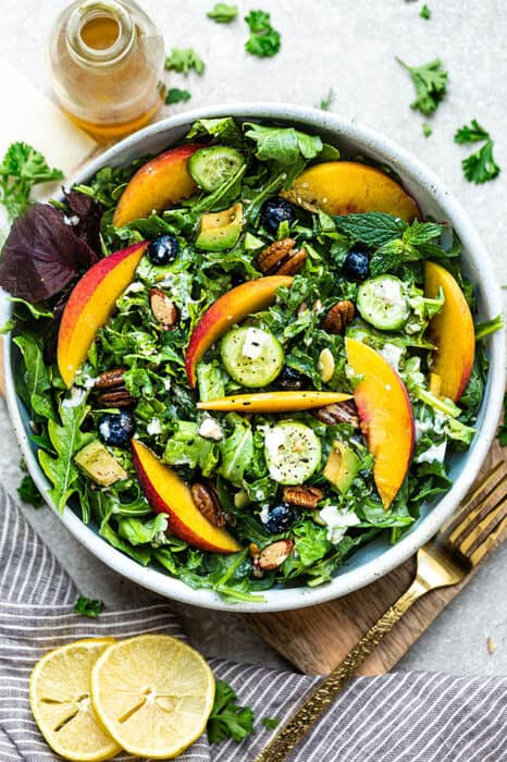 Top view of arugula salad with peaches and blueberries in a white bowl on a wooden cutting board on a grey background