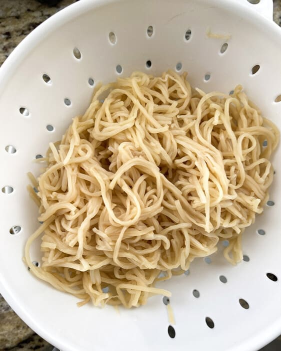 Drained hearts of palm angel hair pasta in a white collander