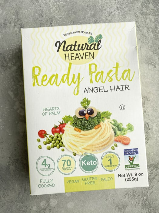 A box of Natural Heaven Hearts of Palm Angel Hair Pasta on a grey background