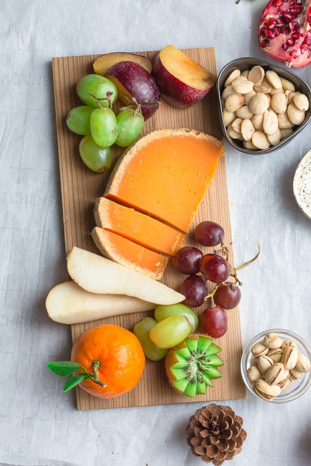 Top view of cheese and fruit on a wooden board