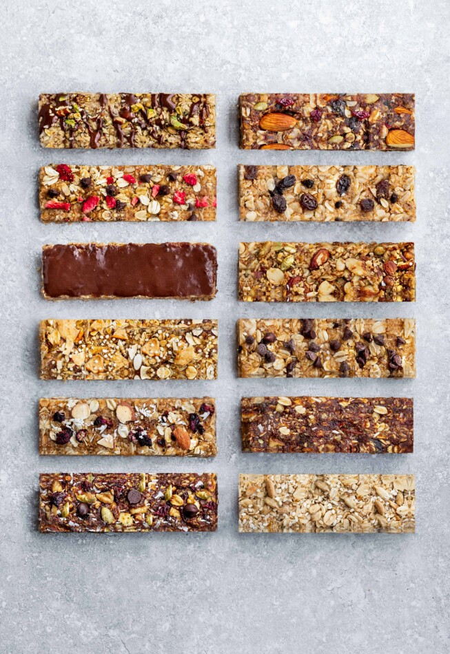 12 Energy Bars of Different Flavors Arranged in Two Columns on a Granite Surface