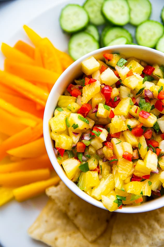 Close-up top shot of a serving of fresh pineapple salsa in a white bowl with sliced cucumbers and bell peppers