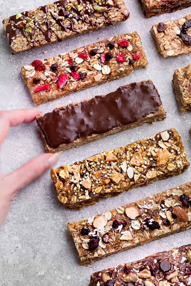 Top view of several varieties of homemade granola bars on a gray background