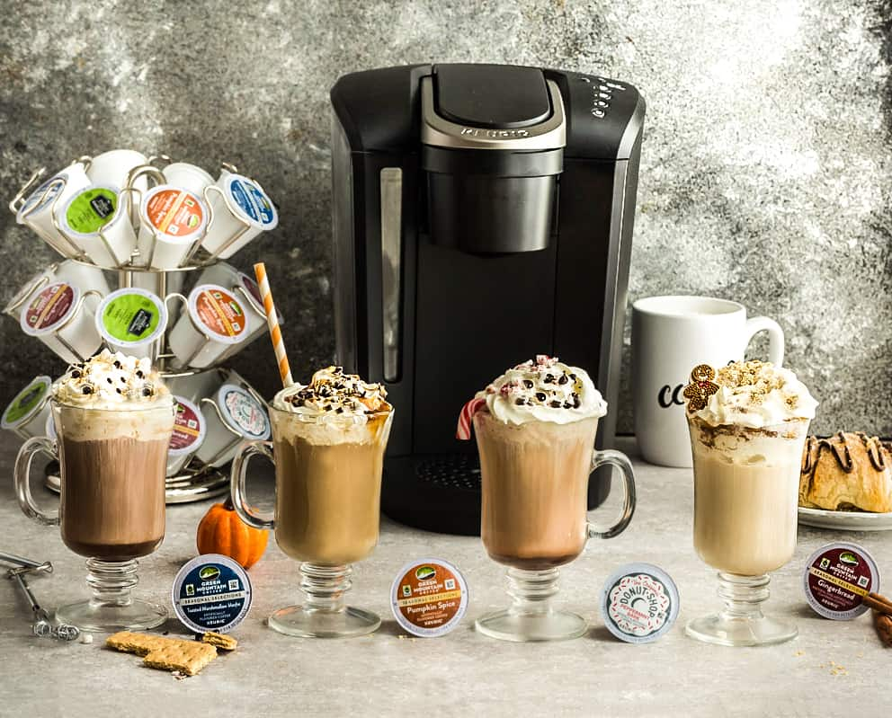 Four homemade lattes in front of a Keurig machine